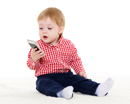 Sweet small baby with mobile phone sits on a white background. photo
