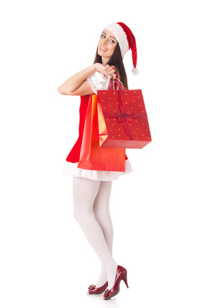 holiday spending: Pretty young woman in Santas suit with shopping bags on a white background.