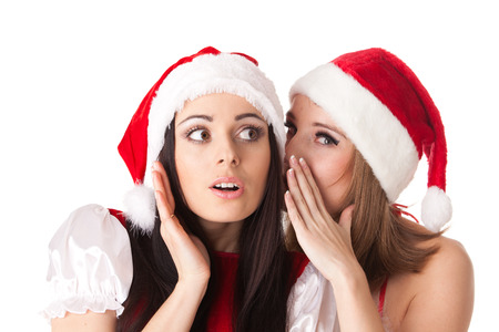 Two young women in Santa costume on a white background. Female secrets. Stock Photo