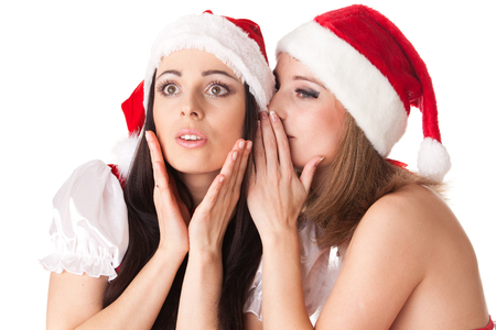 tattle: Two young women in Santa costume on a white background. Female secrets. Stock Photo