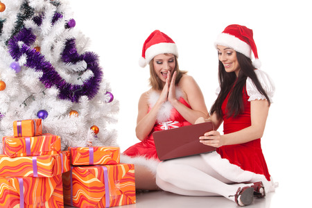 Two girlfriends with laptop and gifts sit near Christmas tree on a white background. photo