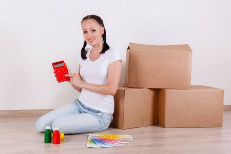 budget repair: The young happy woman sits in a room on the floor with a color guide, paint and calculator near a lot of the boxes. Moving, purchase of new habitation or repair of a room.
