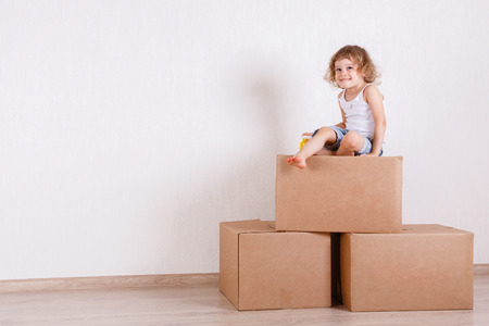 The happy little girl sits in a room on the boxes. Moving, purchase of new habitation or repair of a room. Archivio Fotografico