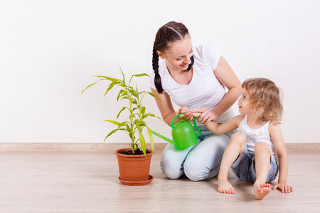 Happy mother and little daughter sit on the floor in a room and water the plant. photo
