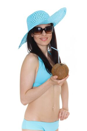 Portrait of young beautiful woman in bikini and sunhat with cocktail in coconut  on a white background. Tropical vacation. photo