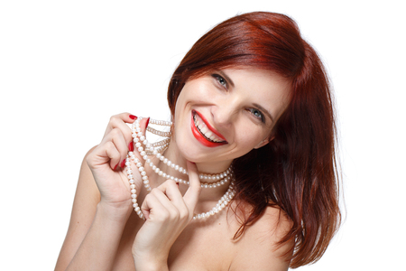 pearly: Portrait of beautiful young  red- haired woman with pearly necklace on a white background.