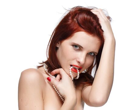 red haired woman: Portrait of beautiful young  red- haired woman with pearly necklace on a white background.