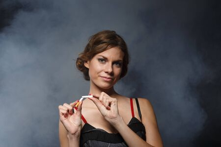quitting: Happy young confident woman, quitting smoking, stands with the broken cigarette on a dark background with smoke. Concept - fight against smoking. Stock Photo