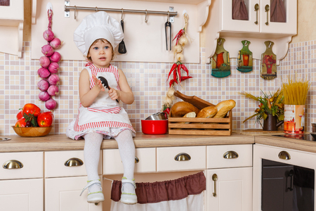 2 year old: Little girl in apron and cap of the cook sits in the kitchen in the house. Mothers helper. 2 year old.