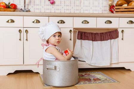 Little girl in apron and cap of the cook sitting  in the kitchen in the house. Mothers helper. 2 year old. photo