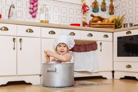 2 year old: Little girl in apron and cap of the cook sitting  in the kitchen in the house. Mothers helper. 2 year old. Stock Photo