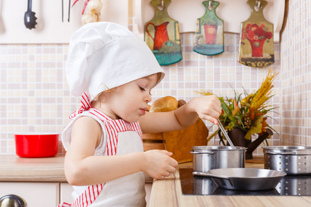 2 year old: Little girl in apron and cap of the cook stands in the kitchen near cooker in the house. Mothers helper. 2 year old.