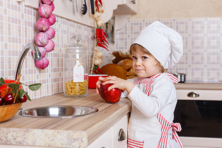 Little girl in apron and cap of the cook with an apple stands in the kitchen near sink at home. Mothers helper. 2 year old. photo