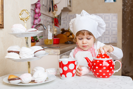 2 year old: Little girl in apron and cap of the cook with sweet desserts sits at the dining table in the kitchen in the house. Mothers helper. 2 year old.