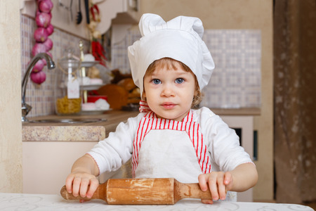 2 year old: Little girl in apron and cap of the cook with rolling pin sits at the dining table in the kitchen in the house. Mothers helper. 2 year old.