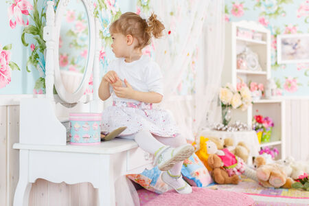 powder room: Pretty little girl playing with cosmetics near dressing table in the room. 2 year old.