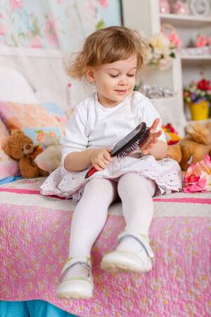 2 year old: Little girl combing hair sits on the bed in children room. 2 year old.