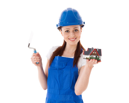 coverall: Young woman in  coverall with trowel and model of house on a white background. Female construction worker. Stock Photo