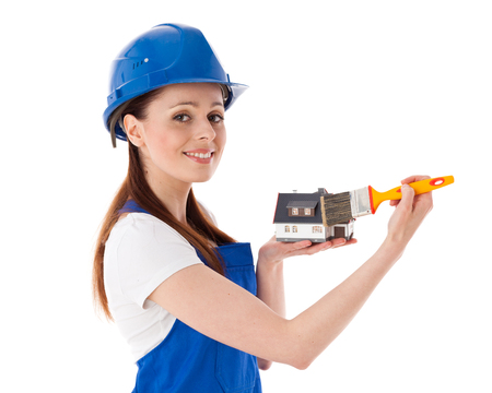 coverall: Young woman in  coverall with paintbrushes and model of house on a white background. Female construction worker. Stock Photo