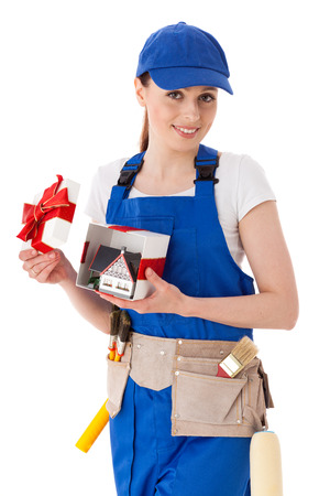 coverall: Young woman in  coverall holds gift box with model of house on a white background. Female construction worker.
