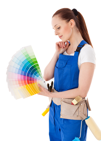 coverall: Young woman in  coverall with a color guide and paintbrushes on a white background. Stock Photo