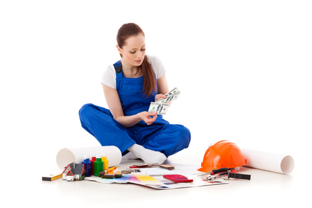 budget repair: Female construction worker on a white background. Stock Photo