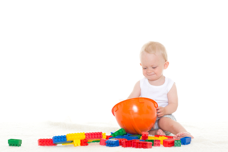Sweet small baby with helmet and toy  building bricks  on a white background. Concept of construction. photo