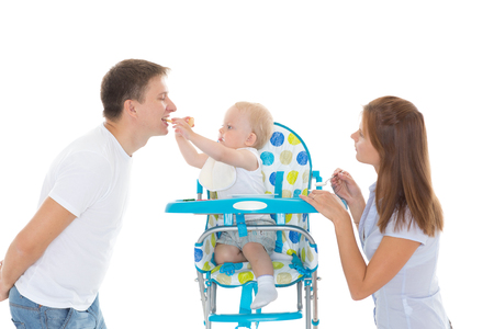 playing with spoon: Young parents feed  baby on a white background. Happy family.