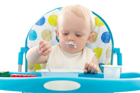 baby with spoon: Sweet baby learning to eat with spoon sits on baby chair on a white background.