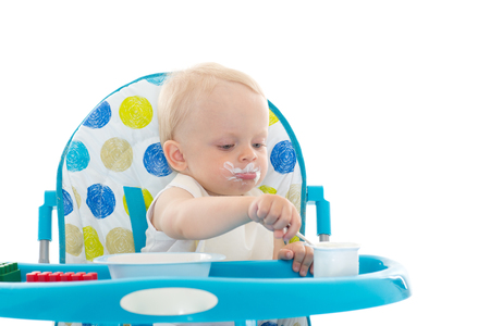 baby on chair: Sweet baby learning to eat with spoon sits on baby chair on a white background.