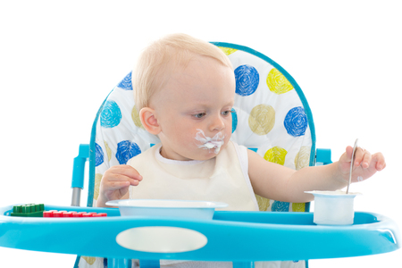 baby chair: Sweet baby learning to eat with spoon sits on baby chair on a white background.
