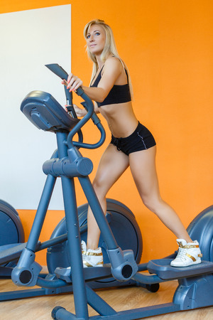 Young sports woman doing exercises on an elliptical trainer in the gym. photo