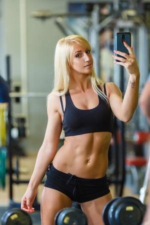 gym girl: Young sports woman with mobile phone in the gym. Fitness.