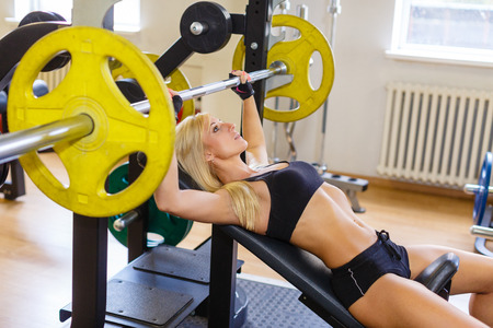 Sports young woman doing exercises with barbell on bench in the gym.  Bar Bench Press. photo