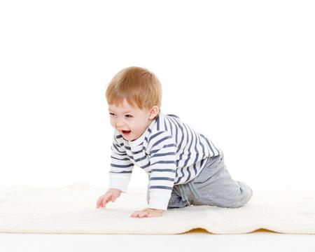 bebe gateando: Dulce pequeño bebé que se arrastra en la alfombra sobre un fondo blanco.
