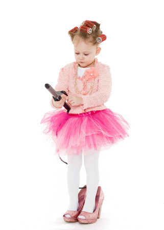 3 year old: Cute little girl with curlers on her head dressed in pink clothes and a huge mothers shoes holds a curling iron on a white background. Little fashionista.  3 year old.