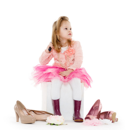 3 year old: Cute little girl in pink clothes sits with hairbrush in the hand  on a white background.  3 year old.
