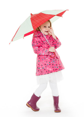 Cute cheerful little girl in raincoat and rubber boots with umbrella stands on a white background.  3 year old. Stock Photo