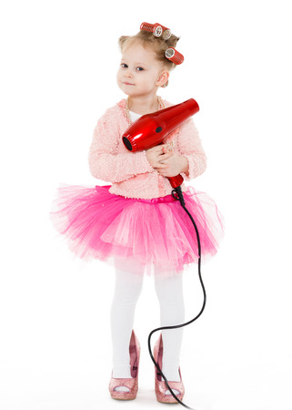 3 year old: Cute little girl with curlers on her head dressed in pink clothes and a huge mothers shoes holds a hair dryer on a white background. Little fashionista.  3 year old. Stock Photo