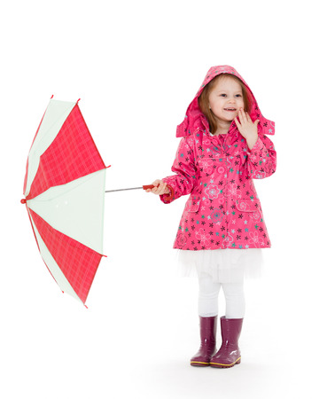 mackintosh: Cute cheerful little girl in raincoat and rubber boots with umbrella stands on a white background.  3 year old. Stock Photo
