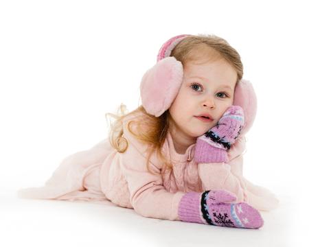 ropa de invierno: Niña muy feliz en ropa de invierno mentiras sobre un fondo blanco. De 3 años.