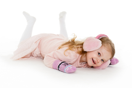 3 year old: Little happy pretty girl in winter clothes lies on a white background. 3 year old. Stock Photo