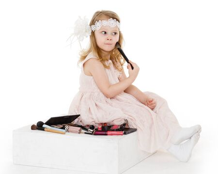3 year old: Pretty little girl playing with cosmetics on a white background. 3 year old.