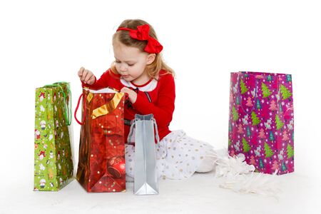 3 year old: Happy pretty little child with shopping bags sits on a white background. 3 year old.