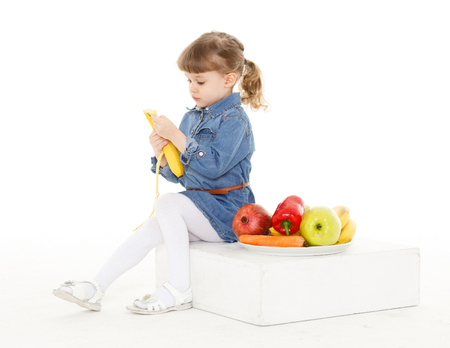 3 year old: Little sweet girl eats fresh fruits and vegetables on a white background. Healthy food. 3 year old.