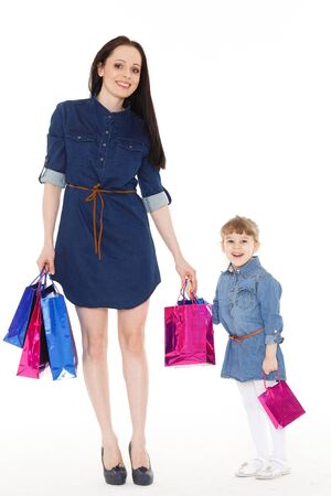 shoppingbag: Young beautiful mother and sweet little daughter standing with shopping bags on a white background. Shopping family.
