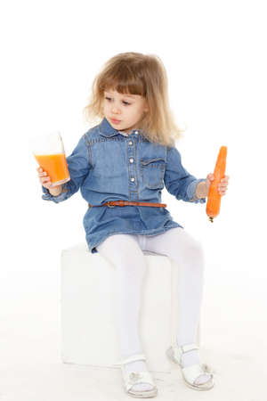 3 year old: Little sweet girl drinks carrot juice on a white background. Healthy food. 3 year old.