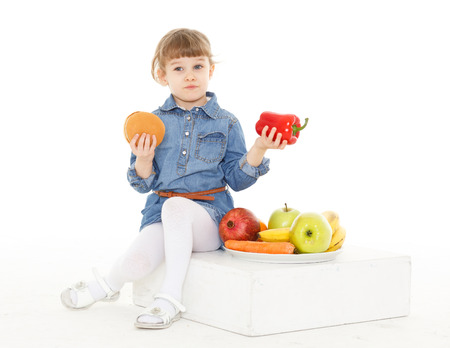 3 year old: Little sweet girl with hamburger, fresh fruits and vegetables on a white background. Healthy and unhealthy food. 3 year old.