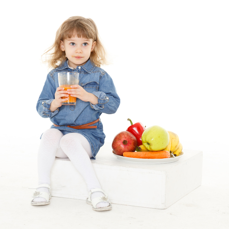 3 year old: Little sweet girl drinks fresh juice on a white background. Healthy food. 3 year old.