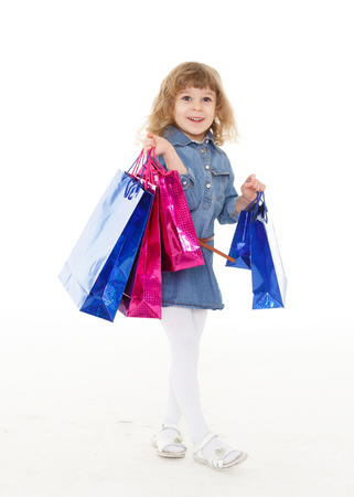 sold small: Happy pretty little child with shopping bags stands on a white background. 3 year old. Stock Photo